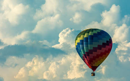 Colorful hot air balloon drifting slowly over cumulonimbus clouds formation.