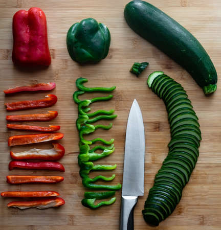 Slices zucchini, red and green bell peppers flat lay on the bamboo cutting board