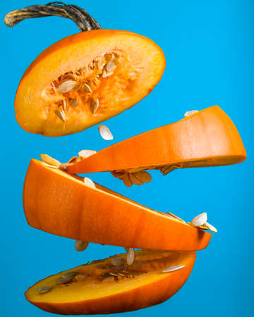 Small orange pumpkin sliced into multiple parts floating in the mid air. Blue Halloween decoration preparation. Food levitation photography. Squash seeds falling to the ground. Gravity denying food.