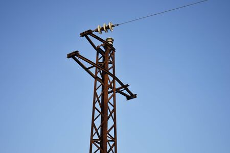 High voltage pole with cable stretched in closeup view