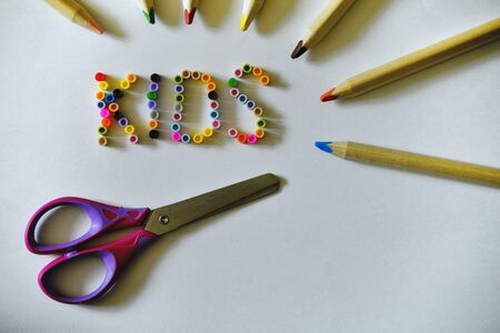 Inscription kids, colorful crayons and children's scissors on light yellow background.