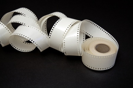 unwound: white film reel on a black background
