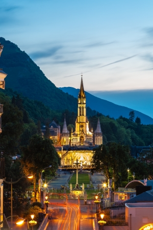 LOURDES, FRANCE – JUNE 06: The Basilica of our Lady of the Rosary on June 06, 2012 in Lourdes in France. Night view on the basilica during the evening procession with candles.