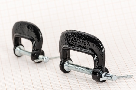 c clamp: Small hand vise c-clamps on a graph paper background