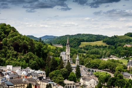 midst: LOURDES – JUNE 06: Basilica at Lourdes in the midst of greenery is seen from afar in Lourdes in France on June 06, 2012 Editorial