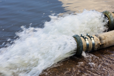 High pressure water flows out of the pipe into the river