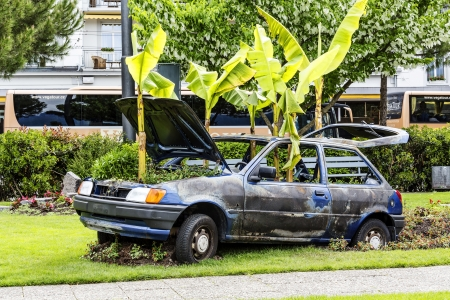third wheel: MONTREUX - MAY 20: Destroyed Ford Fiesta third generation produced from 1989 to 1996 together with the greenery creates the street art on the promenade in Montreux in Switzerland on May 20, 2013
