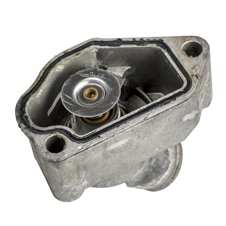 Worn thermostat mounted in the housing of the engine cooling system Stock Photo