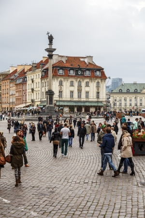 stare miasto: WARSAW - OCTOBER 20: Unidentified tourists on the Castle Square of the Old Town and Kamienica Johna, burned down during the II World War in 1944, rebuilt in 1949 in Warsaw, Poland on October 20, 2013