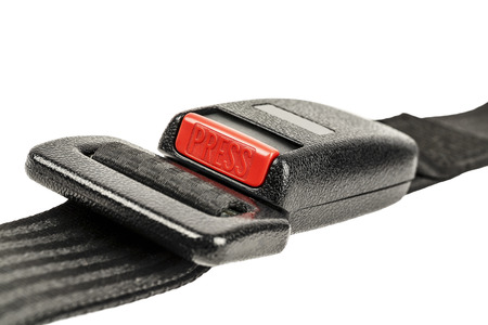 Car safety belt with buckle fastened shown close up on white background photo