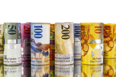 Swiss franc, banknotes rolled up in rolls with a mirror reflection, and on a white background photo