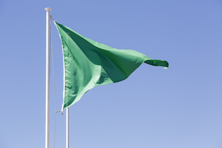 permissible: Green triangular flag against the blue sky of Cote d Azure in Nice, France  Stock Photo