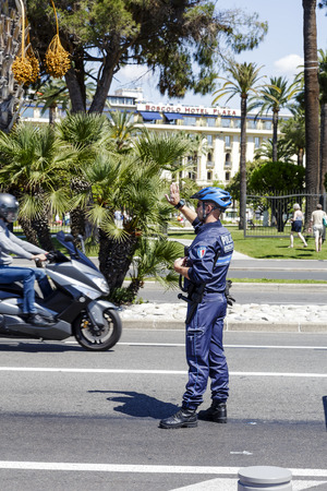 policing: NICE, FRANCE - MAY 18, 2014  Municipal Policeman directs traffic in the city, Municipal Police are one of the three components of French policing, alongside the National Police and the Gendarmerie  Editorial