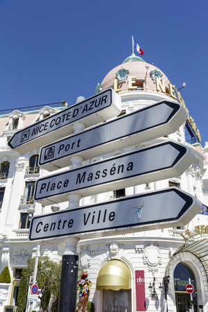 NICE, FRANCE - MAY 24, 2014  Road Signpost against the background of famous and luxury Hotel Negresco, first opened in 1913 facing the Mediterranean sea