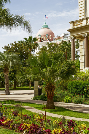 cote d'azure: NICE, FRANCE - MAY 21, 2014  Dome of luxury Hotel Negresco first opened in 1913, view from gardens of Massena Palace Museum of Art and History built between 1898 and 1901, two symbols of Cote d Azure Editorial