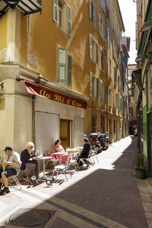 NICE, FRANCE - MAY 18, 2014 People sat down for a little rest and a snack at the tables Au Ble d Azur Restaurant in the Old Town, it shows the lifestyle and architecture detail of Vieille Ville
