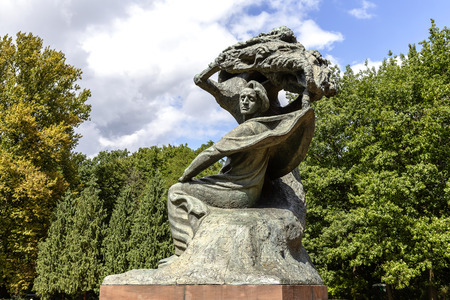 WARSAW, POLAND - AUGUST 25, 2014: Monument to Chopin in Warsaw?s Lazienki public park depict the composer sitting in masovian stylized willow tree, statue made of bronze Editorial
