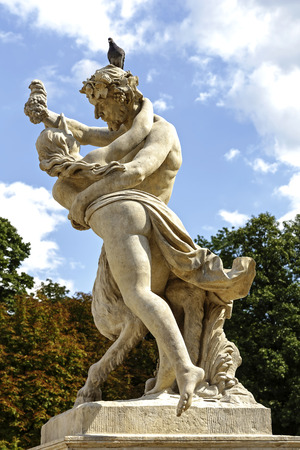 satire: WARSAW, POLAND - AUGUST 25, 2014: Nymph catches a bunch of grapes from the hand of Satire, baroque sculpture of the 18th century, Located in front of the Summer Palace of the King Stanislaw August