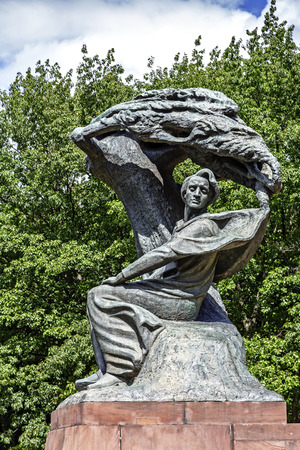 WARSAW, POLAND - AUGUST 25, 2014: Monument to Chopin in Warsaw s Lazienki public park depict the composer sitting in masovian stylized willow tree, statue made of bronze