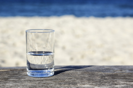 Glass of water which is half-full stands on a wooden table which stands on the sand beach by the sea Imagens