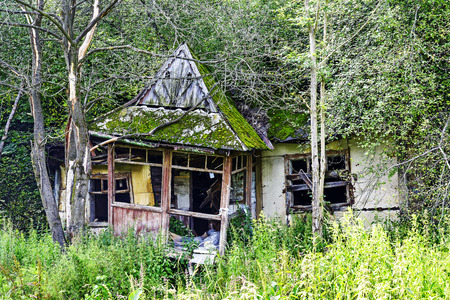badly: Old and very ruined building, forgotten and overgrown by the forest