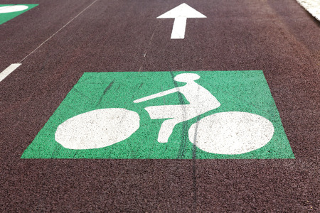 Bicycle road sign, white icon on a green background, and arrow showing the travel direction photo