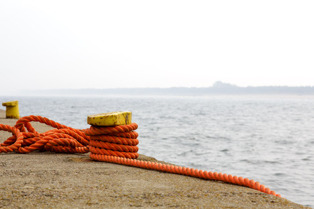 the mooring: Yellow mooring bollard with an orange ropes Stock Photo