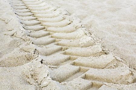 Tractor tires footprint on a sandy beach photo