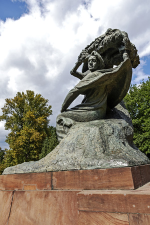 WARSAW, POLAND - AUGUST 25, 2014: Monument to Chopin in Warsaw's Lazienki public park depict the composer sitting in masovian stylized willow tree, statue made of bronze