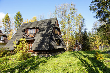 sloping: ZAKOPANE, POLAND - OCTOBER 14, 2014: Building with the sloping roofs with shingles, the architecture of a small wooden house in a stylized form of the hut in the style of Zakopane and Podhale region Editorial