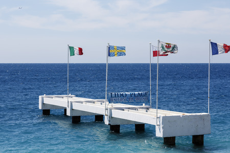 masts: NICE, FRANCE - MAY 18, 2014: Construction made of concrete resembling the remains of the pier, various flags located here on masts blows on the wind, Lido Beach shows their banners here