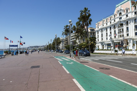 azure coast: NICE, FRANCE - MAY 18, 2014: Bike path along the Promenade des Anglais, the seven kilometers along the coast a favorite place of rest, walking and sport, a symbol of the Azure Coast Editorial