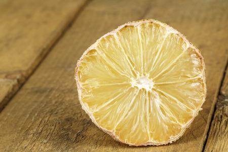 lamentable: Dried lemon lies on wooden background