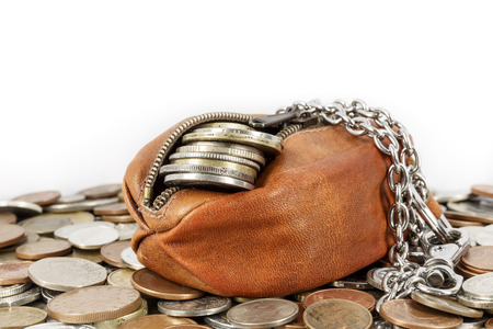 imitation leather: Partially opened purse with a few cents visible in it lies on other coins Stock Photo