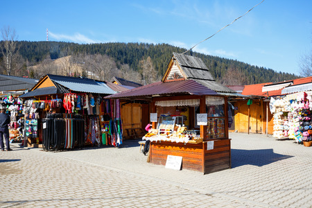 oscypek: ZAKOPANE, POLAND - MARCH 10, 2015: Selling regional food products at the stall situated at the largest marketplace in the city