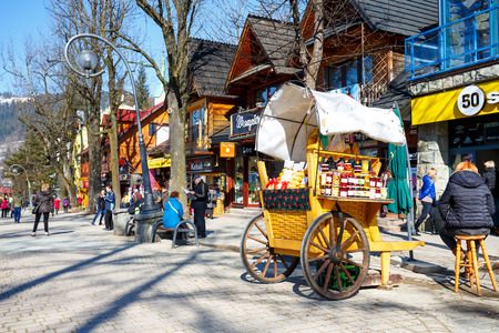 culinary tourism: ZAKOPANE, POLAND - MARCH 09, 2015: Sales of Oscypek cheeses and other regional food products at  Krupowki street, since February 02, 2007 oscypek is Polish regional product protected by EU law Editorial