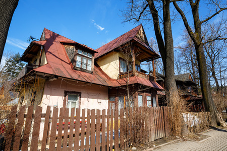 dwelling: ZAKOPANE, POLAND - MARCH 10, 2015: Old dwelling house built around 1900, made of wood in traditional design, then plastered, listed in the municipal register of architectural heritage