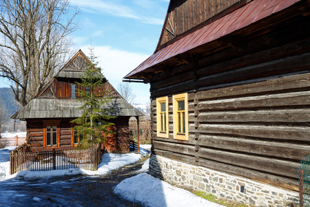 nook: ZAKOPANE, POLAND - MARCH 10, 2015: Architectural nook created by wooden buildings covered with the sloping roofs shows  style of Zakopane and Podhale region