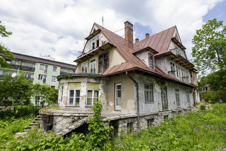 greatly: ZAKOPANE, POLAND - JUNE 14, 2015: Villa called Maryska, built of wood probably at the turn of the 19th and 20th century, nowadays greatly devastated building