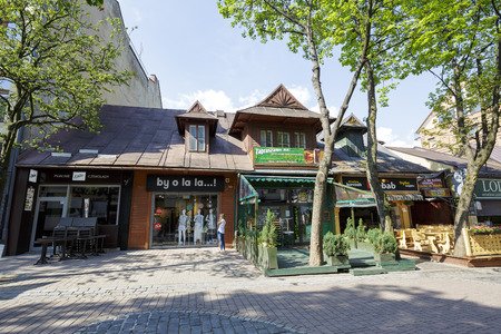 approx: ZAKOPANE, POLAND - JUNE 12, 2015: Residential and commercial building, built of wood approx. 1900, currently operating on the ground floor restaurants and shops