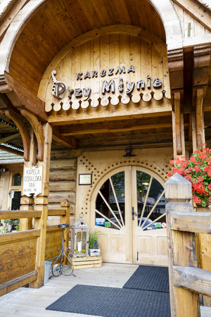 dated: ZAKOPANE, POLAND - JUNE 28, 2015: Main entry to regional restaurant building, called Przy Mlynie, made up of elements derived from the old buildings dated on early 20th century