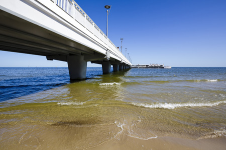 origins: KOLOBRZEG, POLAND - JULY 17, 2015: Reinforced concrete pier with a length of 220 meters and a width of 9 meters in contemporary version was officially opened in 1971, its origins date back to 1881