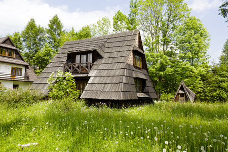 sloping: ZAKOPANE, POLAND - JUNE 10, 2015: Building with the sloping roofs with shingles, the architecture of a small wooden house in a stylized form of the hut in the style of Zakopane and Podhale region Editorial