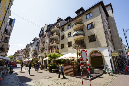 practically: KOLOBRZEG, POLAND - JULY 14, 2015: Tenement houses in the Old Town district are practically new part of the town rebuilt after the devastation of World War II Editorial
