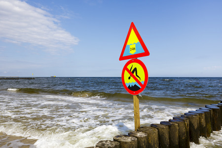 No Jumping and Large Depth warning sign, placed on the breakwater on the beach in Kolobrzeg
