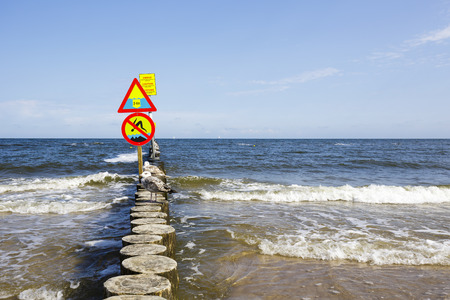 No jumping and large depth warning sign, placed on the breakwater on the beach in Kolobrzeg in Poland