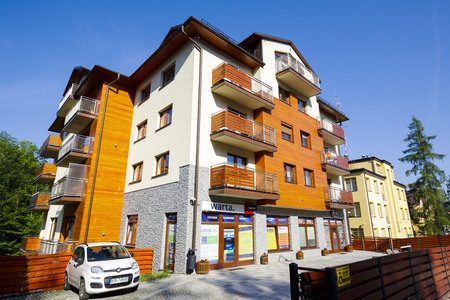 neighboring: ZAKOPANE, POLAND - JUNE 12, 2015: A modern apartment building, stylized to the traditional architecture of the neighboring buildings, located at Jagiellonska street, built early the 21st century