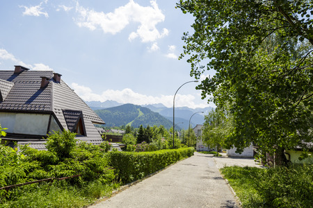 largely: ZAKOPANE, POLAND - JUNE 13, 2015: The view to green areas surrounding the complex of residential buildings at the housing estate called Pardalowka built largely during the years 1979-1995