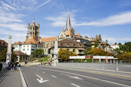 consecrated: LAUSANNE, SWITZERLAND - SEPTEMBER 12, 2015 Lausanne Cathedral Notre Dame seen in the distance, built in Gothic style and it was completed in 1235, was consecrated in 1275