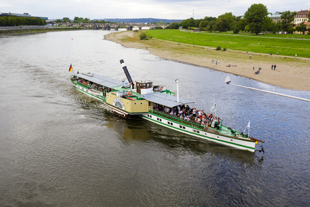 engine powered: DRESDEN, GERMANY - SEPTEMBER 19, 2015: Steamer Diesbar 1884 on waters of the Elbe. It is powered by a steam engine, powered by coal which is considered to be the oldest still running in the world